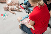 Instructor showing how to safe a life when the baby is choked sitting during the first aid group training indoors