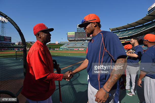 First base coach Alfredo Griffin of the Los Angeles Angels of Anaheim and Domingo Santana of the Houston Astros shake hands before the game at Angel...
