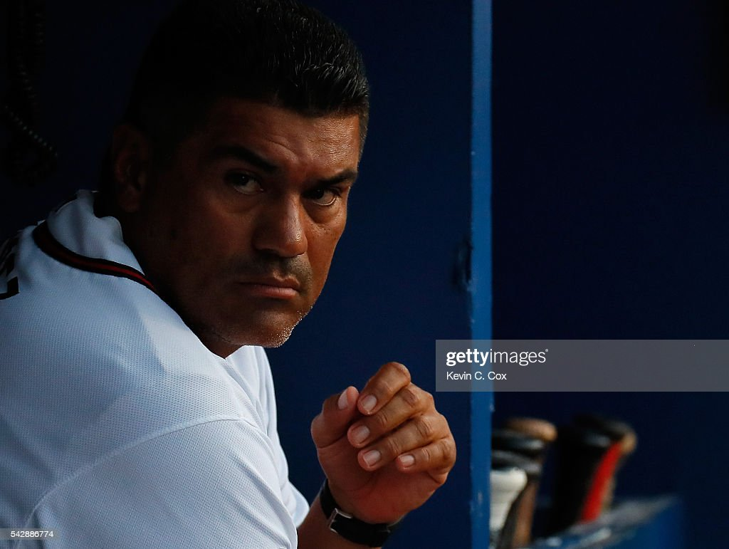 First base coach Eddie Perez #12 looks on during the fourth inning against the New York Mets at Turner Field on June 24, 2016 in Atlanta, Georgia.