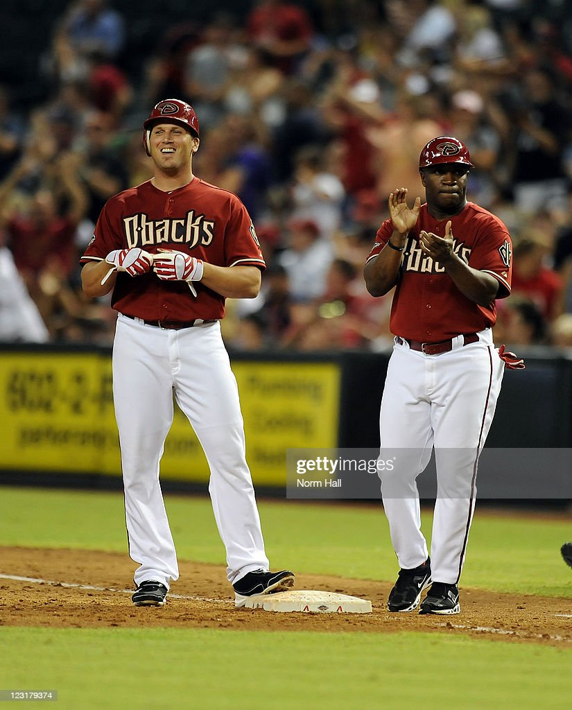 First Base Coach Eric Young #7 of the Arizona Diamondbacks congratulates Sean Burroughs #11 as he smiles at the bench after getting a pinch hit against the Colorado Rockies at Chase Field on August 31, 2011 in Phoenix, Arizona.