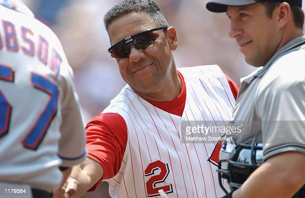 First base coach Jose Cardenal of the Cincinnati Reds shakes hands with bench coach Tom Robson of the New York Mets in front of home plate umpire...