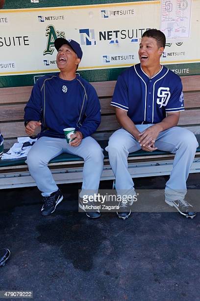 First Base Coach Jose Valentin and Will Venable of the San Diego Padres relax in the dugout prior to the game against the Oakland Athletics at Oco...
