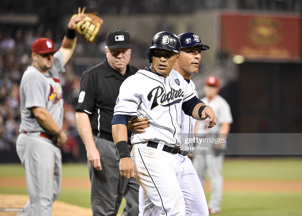 First base coach Jose Valentin #17 of the San Diego Padres, right, walks with Everth Cabrera #2, center, after Cabrera was hit by a pitch during the seventh inning of a baseball game against the St. Louis Cardinals at Petco Park July 30, 2014 in San Diego, California.