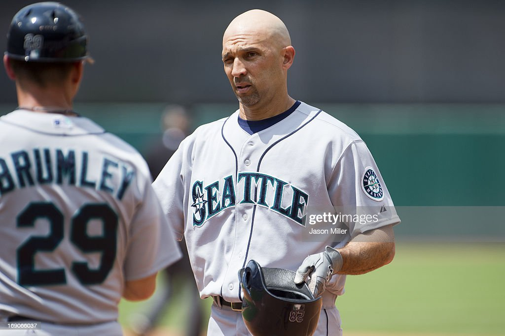 First base coach Mike Brumley #29 talks with <a gi-track='captionPersonalityLinkClicked' href=/galleries/search?phrase=Raul+Ibanez&family=editorial&specificpeople=206118 ng-click='$event.stopPropagation()'>Raul Ibanez</a> #28 of the Seattle Mariners after Ibanez flyer out to right to end the top of the fourth inning against the Cleveland Indians at Progressive Field on May 19, 2013 in Cleveland, Ohio.