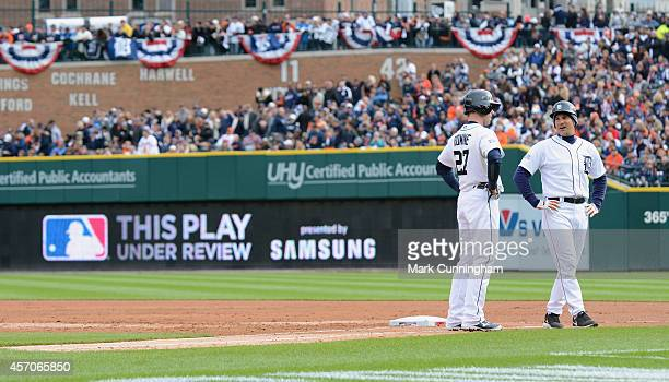 First base coach Omar Vizquel and Andrew Romine of the Detroit Tigers look on during an instant replay review in the second inning of Game Three of...