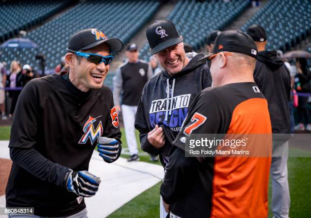 First base coach Perry Hill and Ichiro Suzuki of the Miami Marlins laugh with Mike Redmond of the Colorado Rockies before the game at Coors Field on...