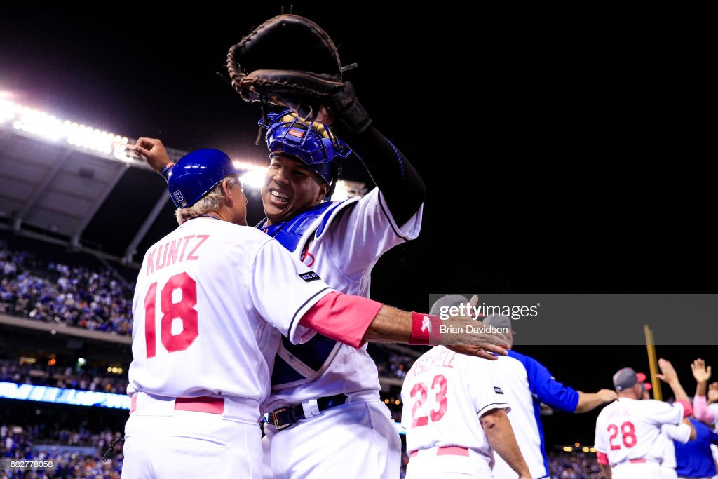 First base coach Rusty Kuntz #18 and Salvador Perez #13 of the Kansas City Royals celebrate defeating the Baltimore Orioles 4-3 at Kauffman Stadium on May 13, 2017 in Kansas City, Missouri. Players are wearing pink to celebrate Mother's Day weekend and support breast cancer awareness.