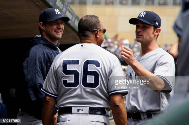 First base coach Tony Pena of the New York Yankees greets Tommy Kahnle and David Robertson in the dugout during the game against the Minnesota Twins...
