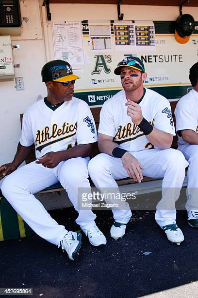 First Base Coach Tye Waller of the Oakland Athletics talks with Craig Gentry in the dugout prior to the game against the Toronto Blue Jays at Oco...