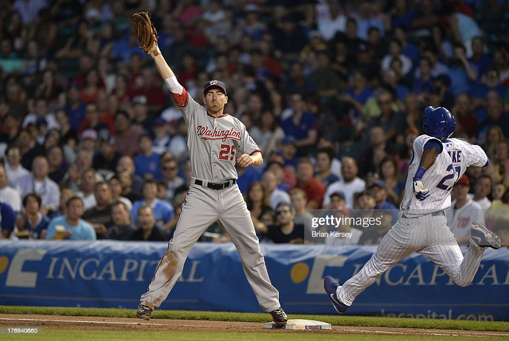 First baseman Adam LaRoche #25 of the Washington Nationals catches the throw from third baseman Ryan Zimmerman #11 to retire Junior Lake #21 of the Chicago Cubs after Lake tried to bunt his way on during the third inning at Wrigley Field on August 19, 2013 in Chicago, Illinois.