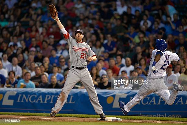 First baseman Adam LaRoche of the Washington Nationals catches the throw from third baseman Ryan Zimmerman to retire Junior Lake of the Chicago Cubs...
