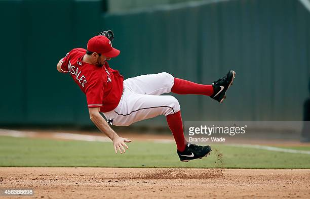 First baseman Adam Rosales of the Texas Rangers falls backwards after fielding a hit by Ramiro Pena of the Atlanta Braves during the third inning of...