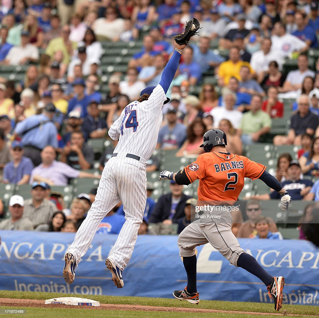 First baseman Anthony Rizzo #44 of the Chicago Cubs leaps off the bag to catch an errant throw by shortstop Starlin Castro (not pictured) as Brandon Barnes #2 of the Houston Astros reaches first base safely during the third inning at Wrigley Field on June 21, 2013 in Chicago, Illinois.