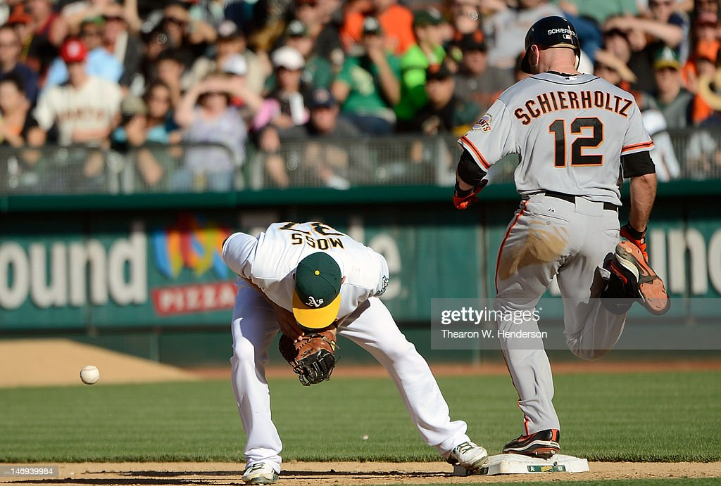 First baseman Brandon Moss #37 of the Oakland Athletics drops the ball, committing an error allowing <a gi-track='captionPersonalityLinkClicked' href=/galleries/search?phrase=Nate+Schierholtz&family=editorial&specificpeople=803208 ng-click='$event.stopPropagation()'>Nate Schierholtz</a> #12 of the San Francisco Giants to reach first base safe in the six inning at O.co Coliseum on June 23, 2012 in Oakland, California.