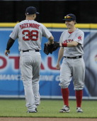 First baseman Brock Holt of the Boston Red Sox taps gloves with Grady Sizemore of the Boston Red Sox after catching a fly ball hit by Ian Kinsler of...