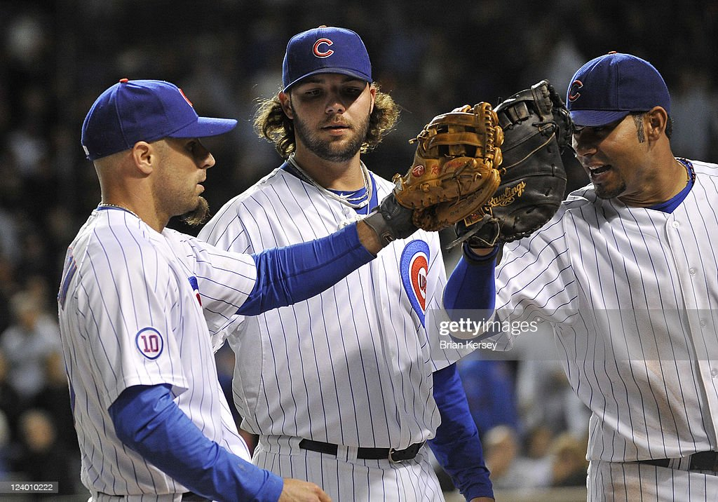 First baseman Carlos Pena #22 (R) of the Chicago Cubs and pitcher James Russell #40 (C) congratulate center fielder <a gi-track='captionPersonalityLinkClicked' href=/galleries/search?phrase=Reed+Johnson&family=editorial&specificpeople=209105 ng-click='$event.stopPropagation()'>Reed Johnson</a> #5 after Johnson threw out Edgar Renteria #16 of the Cincinnati Reds at home plate during the seventh inning at Wrigley Field on September 7, 2011 in Chicago, Illinois. The Cubs defeated the Reds 6-3.