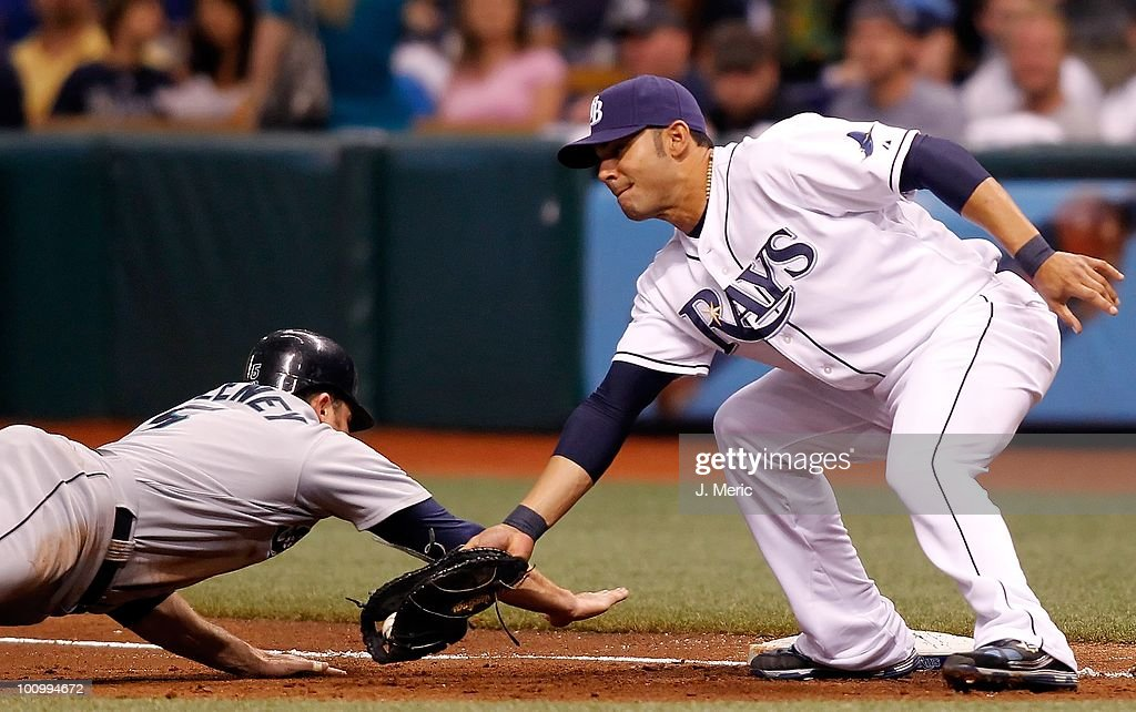 First baseman Carlos Pena #23 of the Tampa Bay Rays takes the throw as Mike Sweeney #5 of the Seattle Mariners gets back safely during the game at Tropicana Field on May 14, 2010 in St. Petersburg, Florida.