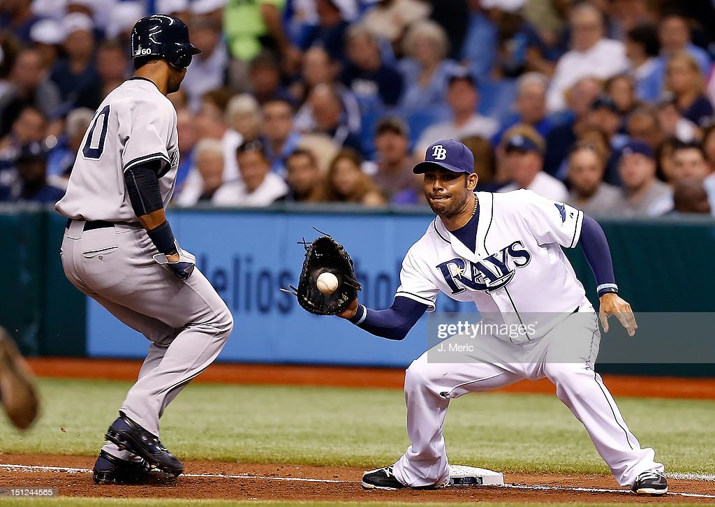 First baseman Carlos Pena #23 of the Tampa Bay Rays takes the throw at first as Chris Dickerson #60 of the New York Yankees gets back safely during the game at Tropicana Field on September 4, 2012 in St. Petersburg, Florida.