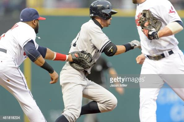 First baseman Carlos Santana of the Cleveland Indians tags out Ichiro Suzuki of the New York Yankees during a rundown in the second inning against...