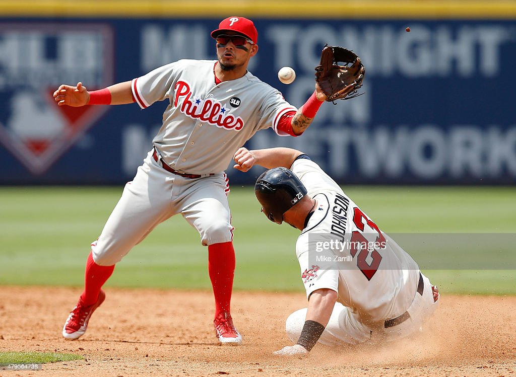 First baseman Chris Johnson of the Atlanta Braves steals second base behind the throw to shortstop Freddy Galvis of the Philadelphia Phillies from...