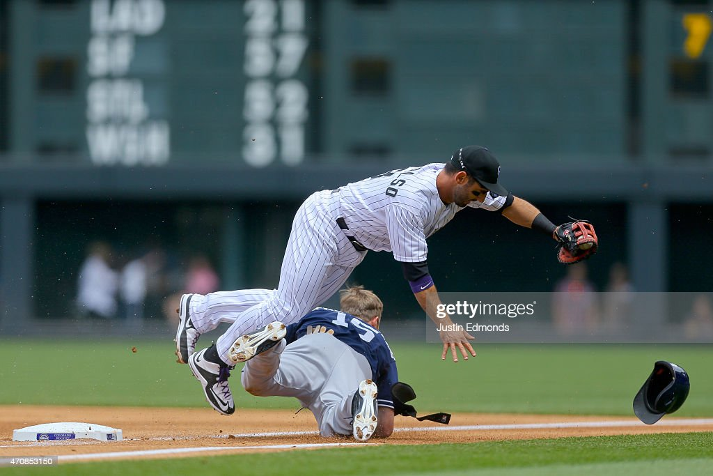 First baseman Daniel Descalso #3 of the Colorado Rockies tumbles over Cory Spangenberg #15 of the San Diego Padres after Spangenberg reached on an infield hit during the first inning at Coors Field on April 23, 2015 in Denver, Colorado.