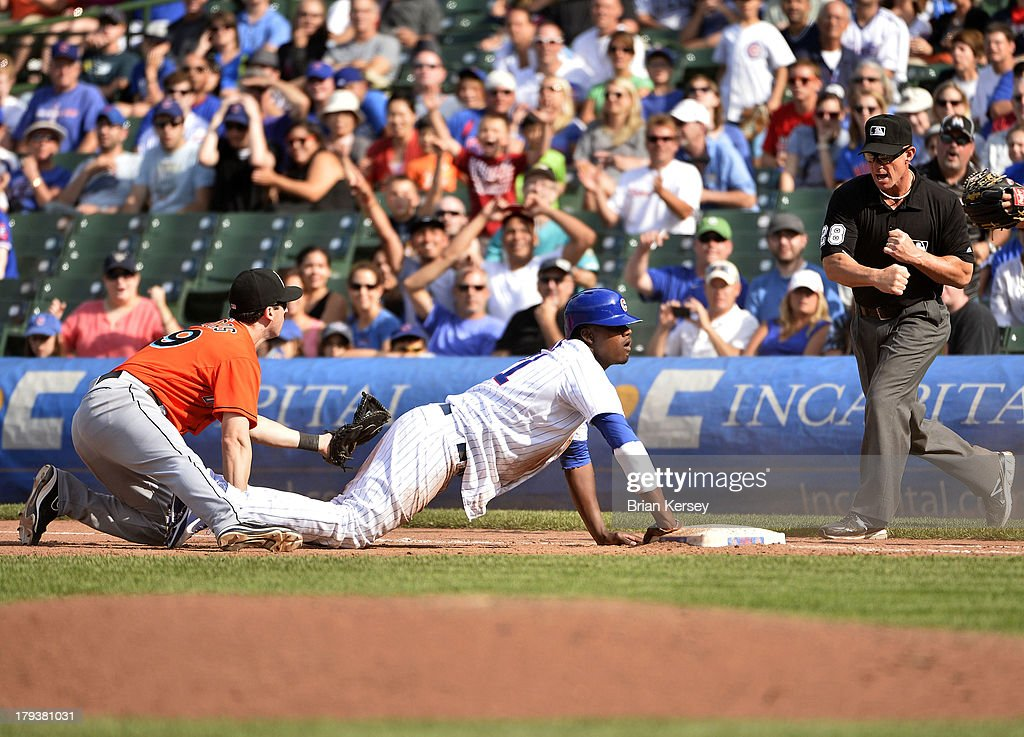 First baseman Ed Lucas #59 of the Miami Marlins (L) and Junior Lake #21 of the Chicago Cubs react as first base umpire <a gi-track='captionPersonalityLinkClicked' href=/galleries/search?phrase=Jim+Wolf&family=editorial&specificpeople=234814 ng-click='$event.stopPropagation()'>Jim Wolf</a> #28 calls Lake out at first base after Darwin Barney #15 hit into a double play to end the ninth inning at Wrigley Field on September 2, 2013 in Chicago, Illinois The Marlins defeated the Cubs 4-3.
