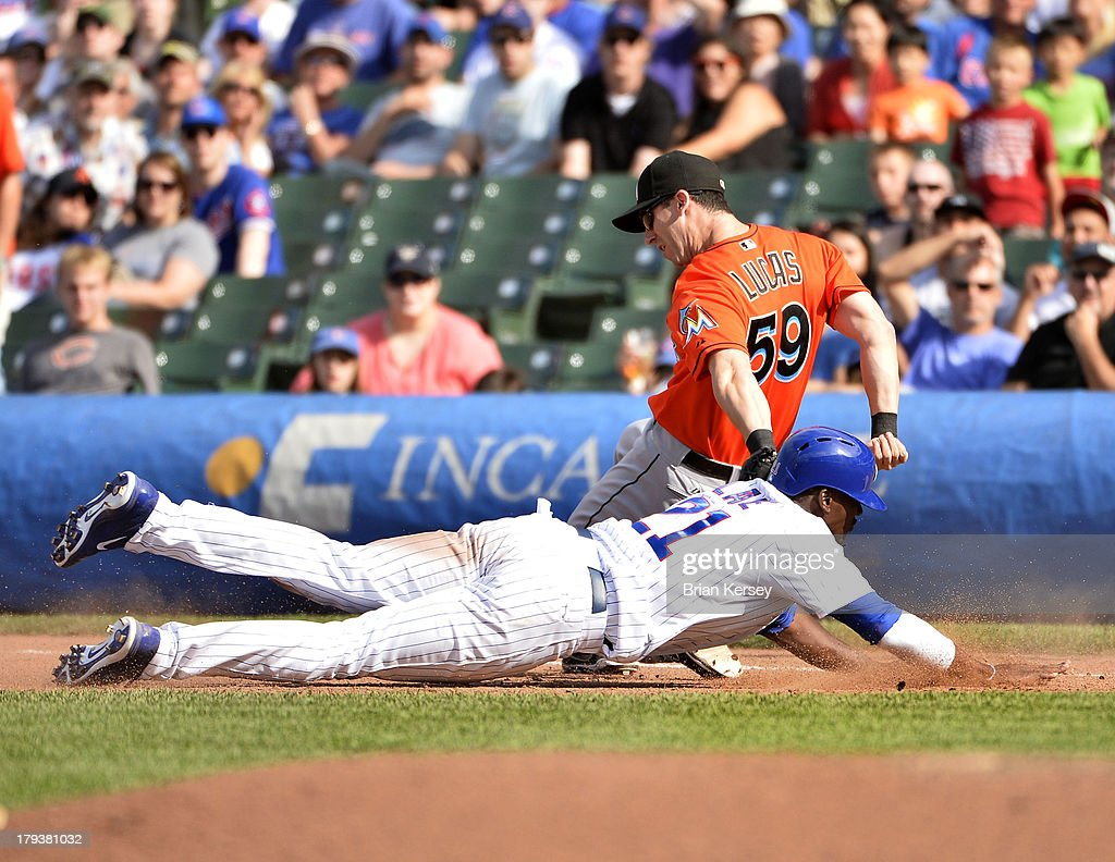 First baseman Ed Lucas #59 of the Miami Marlins tags out Junior Lake #21 of the Chicago Cubs at first base after Darwin Barney #15 hit into a double play to end the ninth inning at Wrigley Field on September 2, 2013 in Chicago, Illinois The Marlins defeated the Cubs 4-3.