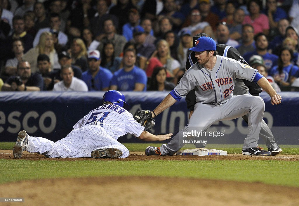 First baseman <a gi-track='captionPersonalityLinkClicked' href=/galleries/search?phrase=Ike+Davis&family=editorial&specificpeople=2349664 ng-click='$event.stopPropagation()'>Ike Davis</a> #29 of the New York Mets (R) tags Steve Clevenger #51 of the Chicago Cubs on a pickoff play at first base during the eighth inning at Wrigley Field on June 26, 2012 in Chicago, Illinois. Clevenger was called safe and Davis was ejected for arguing with first base umpire Manny Gonzalez #79.