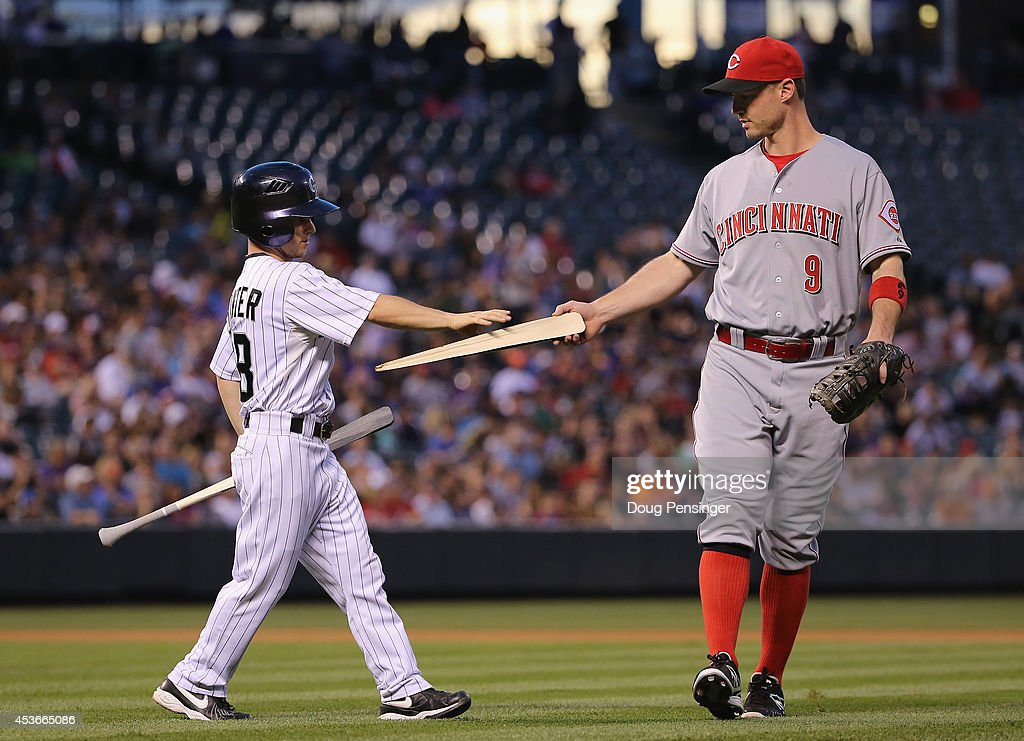 First baseman Jack Hannahan #9 of the Cincinnati Reds hands a piece of the broken bat of Corey Dickerson #6 of the Colorado Rockies to the bat boy at Coors Field on August 15, 2014 in Denver, Colorado.