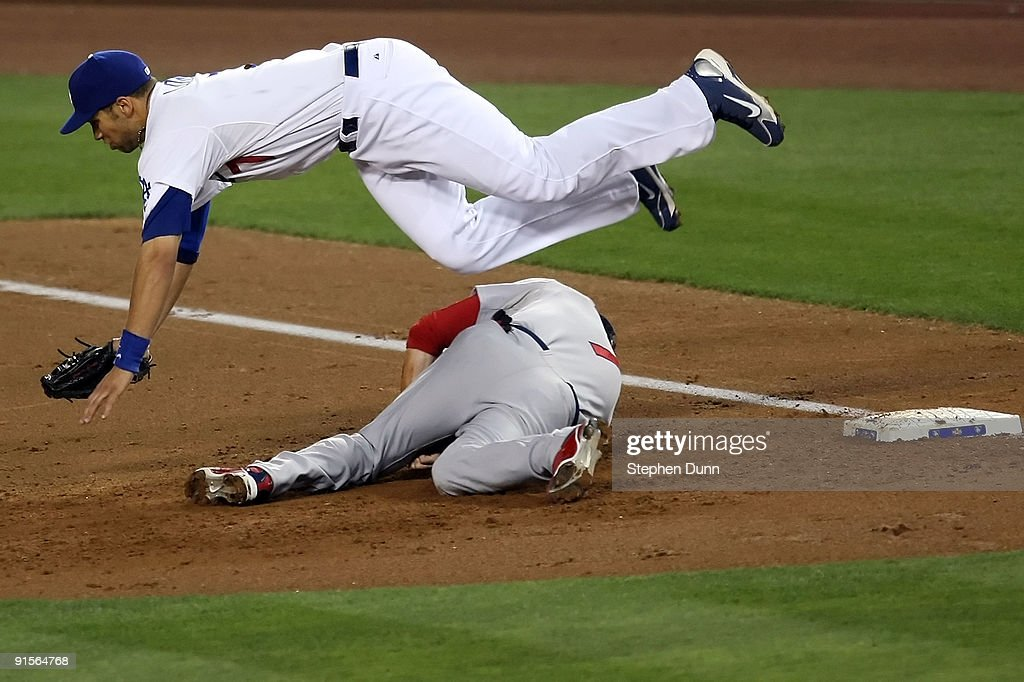 First baseman James Loney #7 of the Los Angeles Dodgers dives over Mark DeRosa #7 of the St. Louis Cardinals to catch the ball in the second inning in Game One of the NLDS during the 2009 MLB Playoffs at Dodger Stadium on October 7, 2009 in Los Angeles, California.