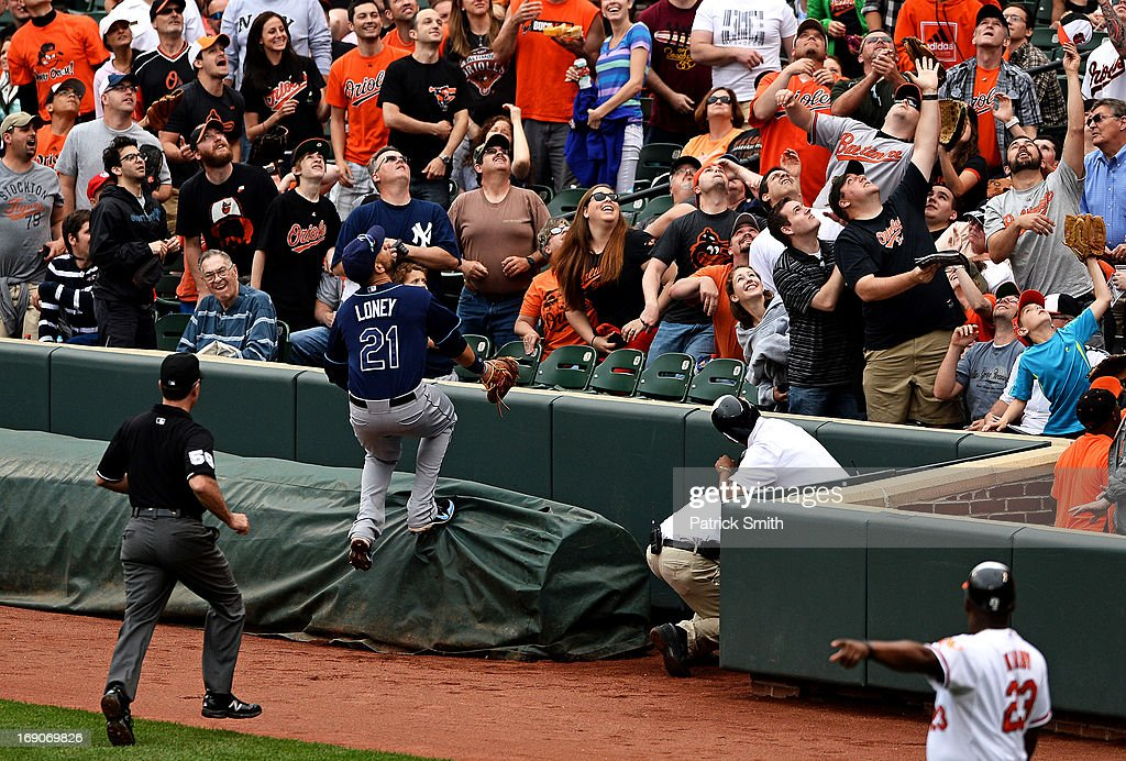 First baseman James Loney #21 of the Tampa Bay Rays runs onto the rain tarp in attempt to judge catching a Baltimore Orioles foul ball in the fourth inning at Oriole Park at Camden Yards on May 19, 2013 in Baltimore, Maryland. The Tampa Bay Rays won, 3-1.