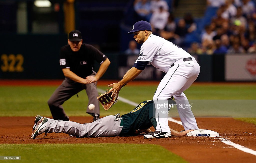 First baseman <a gi-track='captionPersonalityLinkClicked' href=/galleries/search?phrase=James+Loney&family=editorial&specificpeople=636293 ng-click='$event.stopPropagation()'>James Loney</a> #21 of the Tampa Bay Rays takes the throw at first as infielder Josh Donaldson #20 of the Oakland Athletics gets back safely during the game at Tropicana Field on April 20, 2013 in St. Petersburg, Florida.
