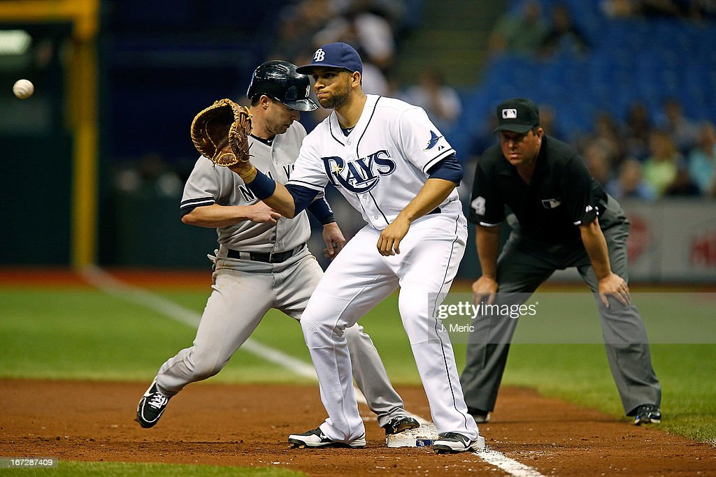 First baseman <a gi-track='captionPersonalityLinkClicked' href=/galleries/search?phrase=James+Loney&family=editorial&specificpeople=636293 ng-click='$event.stopPropagation()'>James Loney</a> #21 of the Tampa Bay Rays takes the throw at first as <a gi-track='captionPersonalityLinkClicked' href=/galleries/search?phrase=Jayson+Nix&family=editorial&specificpeople=836132 ng-click='$event.stopPropagation()'>Jayson Nix</a> #17 of the New York Yankees gets back safely during the game at Tropicana Field on April 23, 2013 in St. Petersburg, Florida.