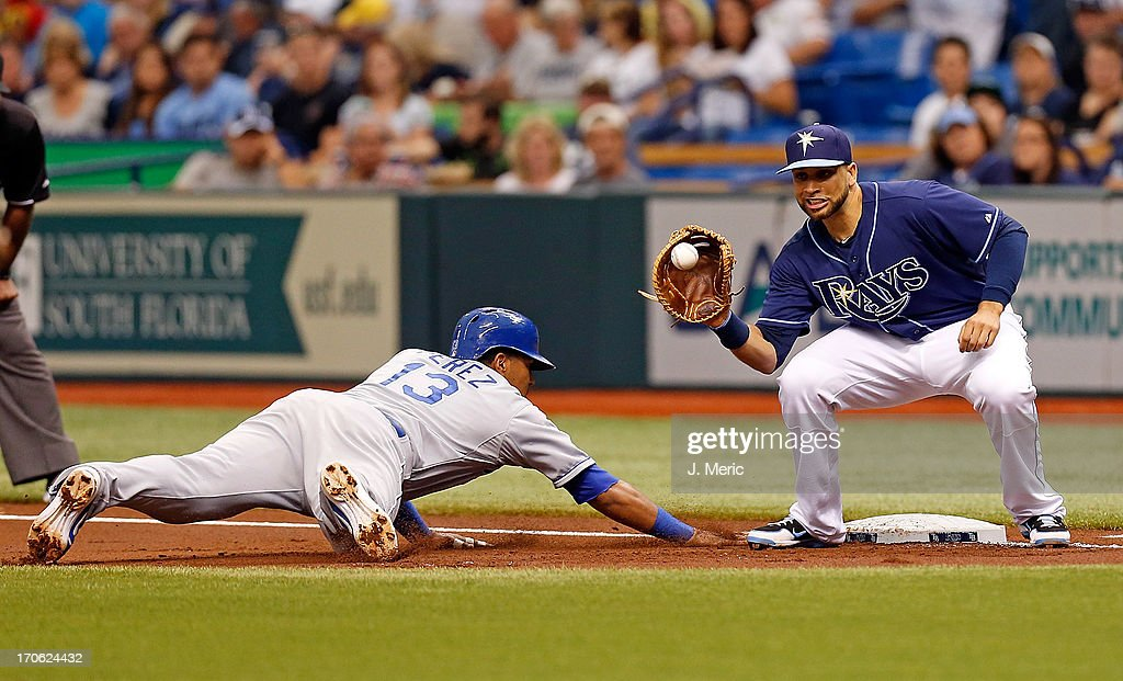 First baseman James Loney #21 of the Tampa Bay Rays takes the throw at first as catcher Salvador Perez #13 of the Kansas City Royals gets back safely during the game at Tropicana Field on June 15, 2013 in St. Petersburg, Florida.