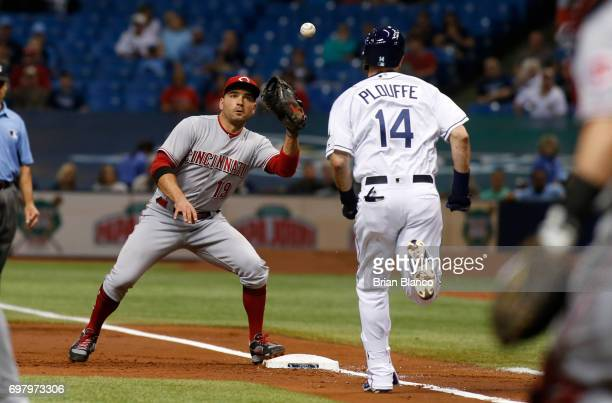 First baseman Joey Votto of the Cincinnati Reds hauls in the throw from pitcher Scott Feldman for the pout at first base on Trevor Plouffe of the...