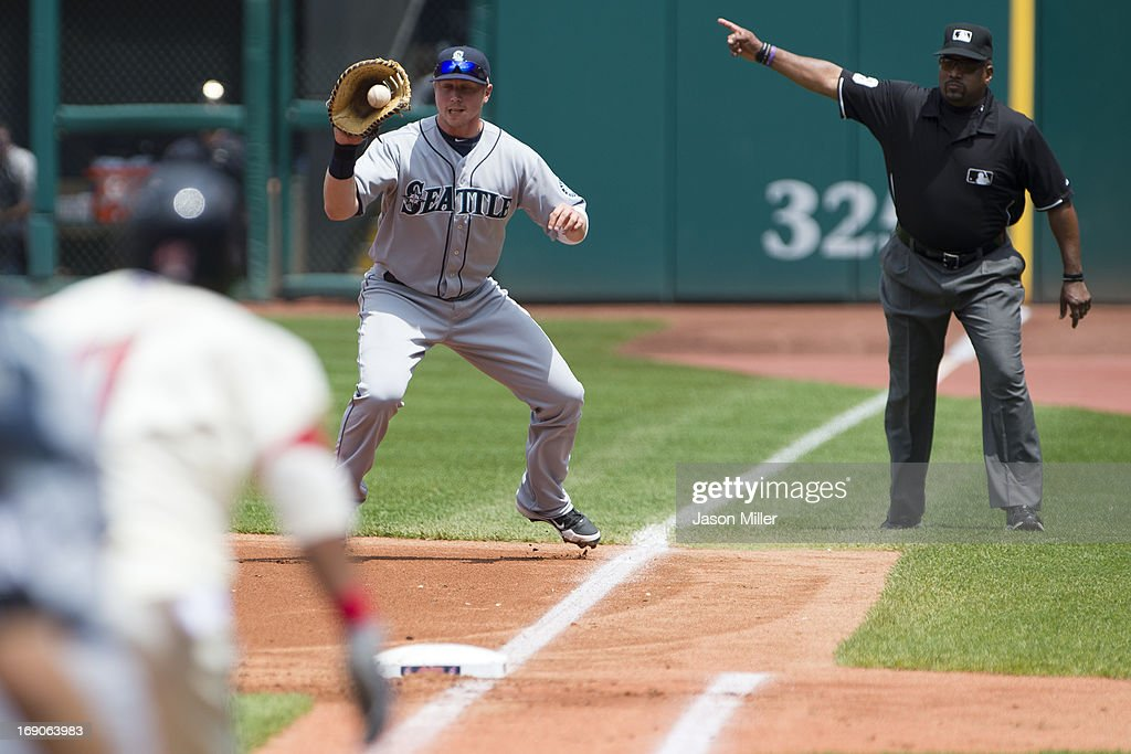 First baseman <a gi-track='captionPersonalityLinkClicked' href=/galleries/search?phrase=Justin+Smoak&family=editorial&specificpeople=2350583 ng-click='$event.stopPropagation()'>Justin Smoak</a> #17 of the Seattle Mariners fields a ground ball hit by Carlos Santana #41 of the Cleveland Indians as umpire <a gi-track='captionPersonalityLinkClicked' href=/galleries/search?phrase=Laz+Diaz&family=editorial&specificpeople=541436 ng-click='$event.stopPropagation()'>Laz Diaz</a> #63 makes the fair ball call during the first inning at Progressive Field on May 19, 2013 in Cleveland, Ohio.