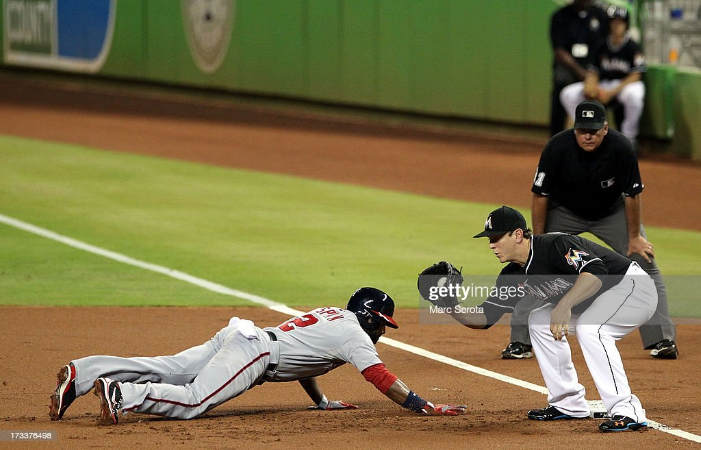 First baseman Logan Morrison #5 of the Miami Marlins attempts to pick off <a gi-track='captionPersonalityLinkClicked' href=/galleries/search?phrase=Denard+Span&family=editorial&specificpeople=835844 ng-click='$event.stopPropagation()'>Denard Span</a> #2 of the Washington Nationals at Marlins Park on July 12, 2013 in Miami, Florida.The Marlins defeated the Nationals 8-3.