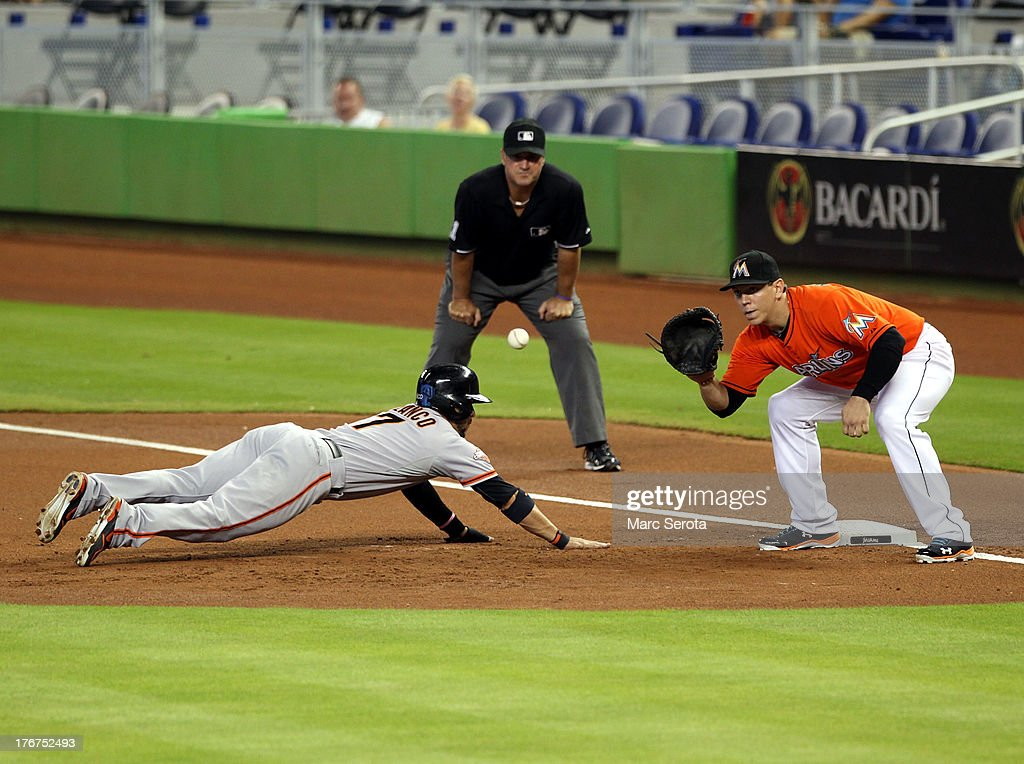 First baseman Logan Morrison #5 of the Miami Marlins attempts to pick off <a gi-track='captionPersonalityLinkClicked' href=/galleries/search?phrase=Gregor+Blanco&family=editorial&specificpeople=4137600 ng-click='$event.stopPropagation()'>Gregor Blanco</a> #7 of the San Francisco Giants at Marlins Park on August 18, 2013 in Miami, Florida.