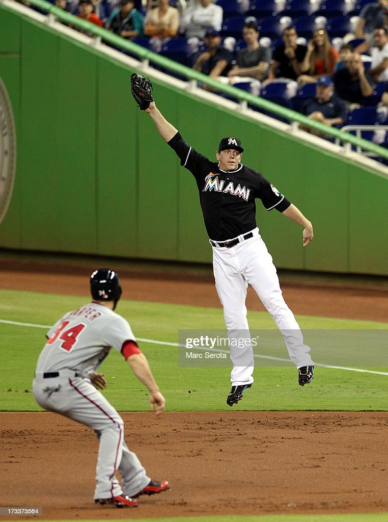 First baseman Logan Morrison #5 of the Miami Marlins leaps for a ball in front of Bryce Harper #34 of the Washington Nationals during the second inning at Marlins Park on July 12, 2013 in Miami, Florida.