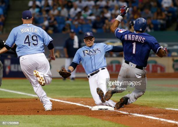 First baseman Logan Morrison of the Tampa Bay Rays gets the out at first base on Elvis Andrus of the Texas Rangers as pitcher Tommy Hunter runs in to...