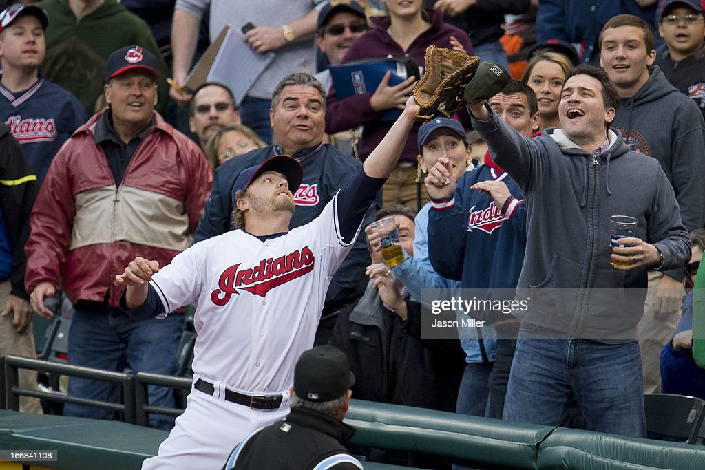 First baseman <a gi-track='captionPersonalityLinkClicked' href=/galleries/search?phrase=Mark+Reynolds&family=editorial&specificpeople=2343799 ng-click='$event.stopPropagation()'>Mark Reynolds</a> #12 of the Cleveland Indians dives into the crowd to catch a pop fly hit by Mike Napoli #12 of the Boston Red Sox during the second inning at Progressive Field on April 17, 2013 in Cleveland, Ohio.