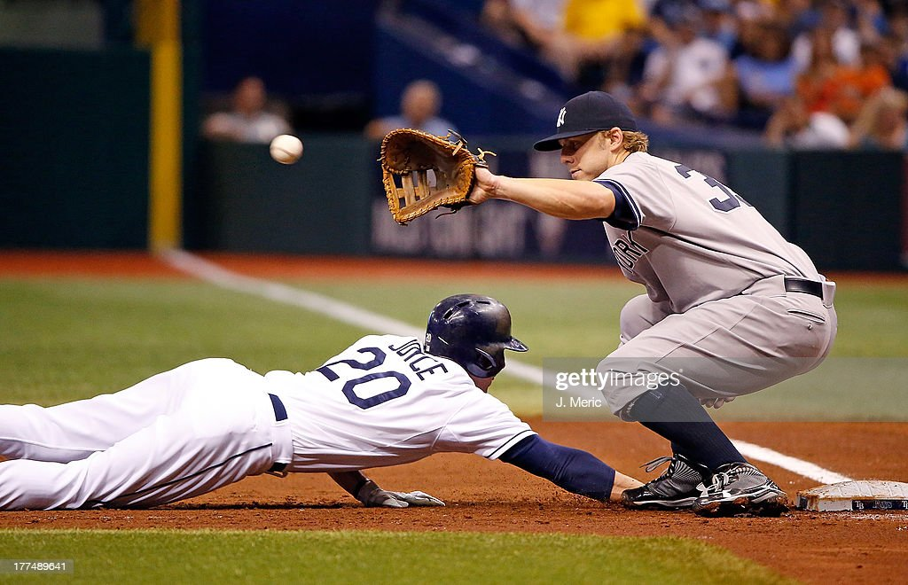 First baseman <a gi-track='captionPersonalityLinkClicked' href=/galleries/search?phrase=Mark+Reynolds+-+Baseball+Player&family=editorial&specificpeople=2343799 ng-click='$event.stopPropagation()'>Mark Reynolds</a> #39 of the New York Yankees takes the throw as Matt Joyce #20 of the Tampa Bay Rays gets back safely during the game at Tropicana Field on August 23, 2013 in St. Petersburg, Florida.