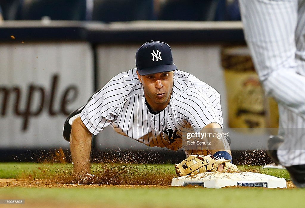 First baseman Mark Teixeira #25 of the New York Yankees dives to first base to get Josh Reddick #22 of the Oakland Athletics during the eighth inning of a MLB baseball game at Yankee Stadium on July 8, 2015 in the Bronx borough of New York City. The Yankees defeated the A's 5-4.