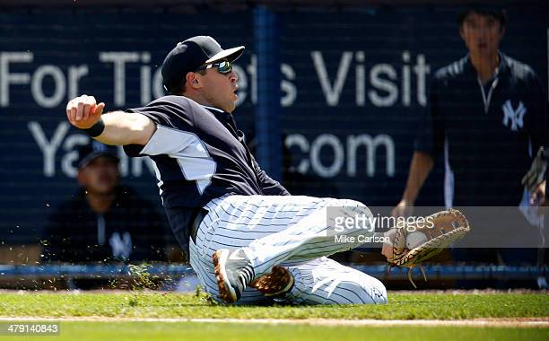 First baseman Mark Texieira of the New York Yankees makes a catch on a foul ball against the Atlanta Braves during a spring training game at George M...