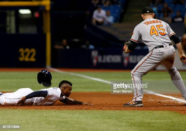 First baseman Mark Trumbo of the Baltimore Orioles catches Tim Beckham of the Tampa Bay Rays doubling off first base to end the seventh inning of a...