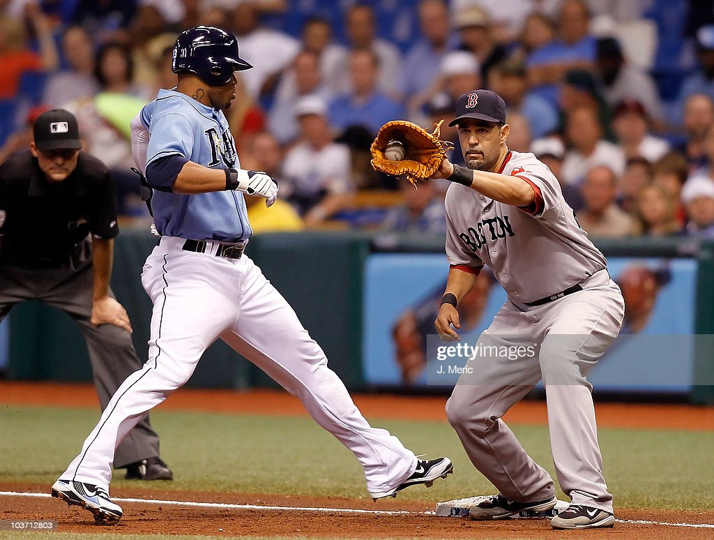First baseman Mike Lowell of the Boston Red Sox takes the throw at first as outfielder Carl Crawford of the Tampa Bay Rays gets back safely during...