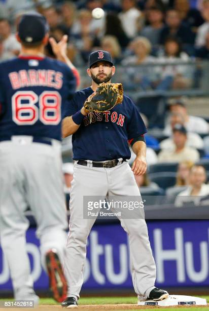 First baseman Mitch Moreland takes a throw from pitcher Matt Barnes for an out on a ball hit to Barnes in an MLB baseball game against the New York...