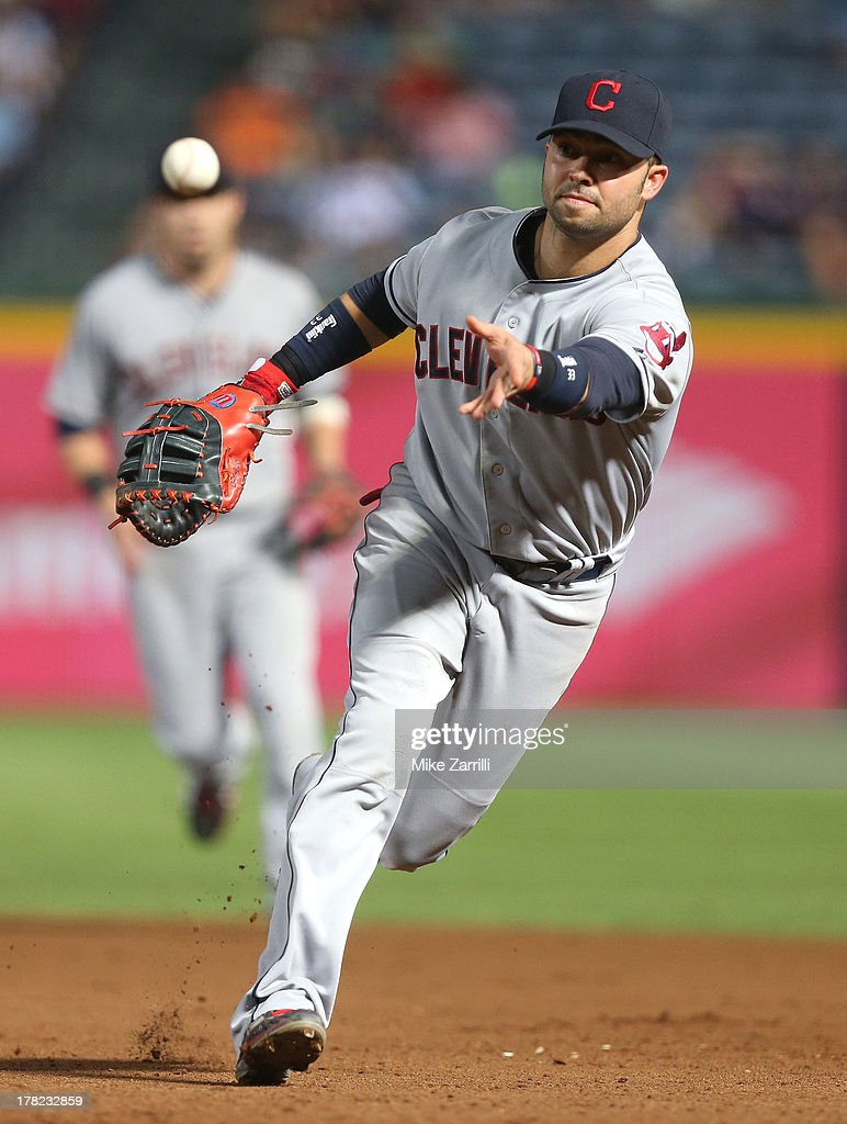 First baseman <a gi-track='captionPersonalityLinkClicked' href=/galleries/search?phrase=Nick+Swisher&family=editorial&specificpeople=206417 ng-click='$event.stopPropagation()'>Nick Swisher</a> #33 of the Cleveland Indians lobs the ball towards first base during the game against the Atlanta Braves at Turner Field on August 27, 2013 in Atlanta, Georgia.