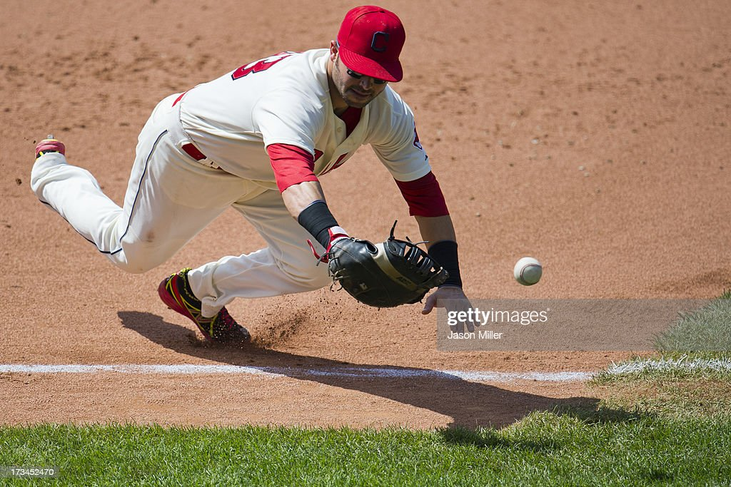 First baseman <a gi-track='captionPersonalityLinkClicked' href=/galleries/search?phrase=Nick+Swisher&family=editorial&specificpeople=206417 ng-click='$event.stopPropagation()'>Nick Swisher</a> #33 of the Cleveland Indians tries to field a foul ball hit by David Lough #7 of the Kansas City Royals during the eighth inning at Progressive Field on July 14, 2013 in Cleveland, Ohio. The Indians defeated the Royals 6-4.