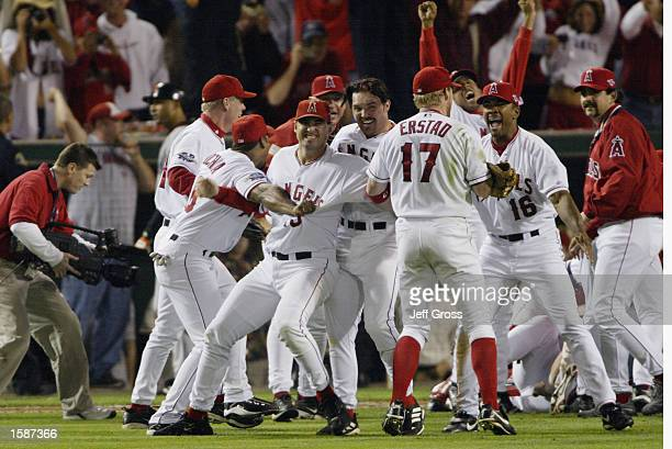 First baseman Scott Spiezio centerfielder Darin Erstad and leftfielder Garret Anderson of the Anaheim Angels celebrate with their team after the...